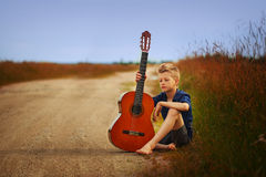 Teenage boy with acoustic guitar on country road. Teenage boy with acoustic guitar on country road stock photography