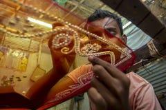 A teenage boy adds detail to a traditional Jamdani saree in Mirpur Benarashi Palli, Dhaka, Bangladesh. stock images