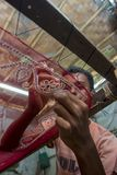 A teenage boy adds detail to a traditional Jamdani saree in Mirpur Benarashi Palli, Dhaka, Bangladesh. royalty free stock image