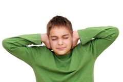 Teenage boy with arms on ears Stock Image