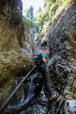 Teenage boy backpacker going down in a gorge Royalty Free Stock Photos