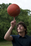 Teenage boy with basketball. Teenage boy spins a basketball on his finger Stock Images