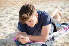 Teenage boy at the beach. Teenage boy laying on a beach using a mobile phone Stock Image