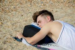 Teenage boy at the beach. Teenage boy laying on a stoney beach Royalty Free Stock Image
