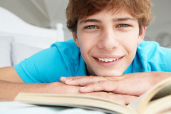 Teenage boy on bed reading a book Stock Image