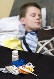 Teenage boy in bed sick Stock Image