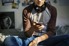 Teenage boy in a bedroom listening to music through his smartphone stock photos