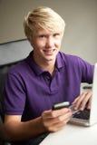 Teenage Boy in Bedroom On Mobile Phone Stock Photo