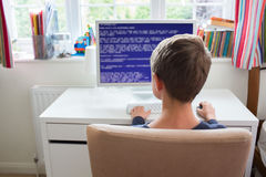 Teenage Boy In Bedroom Writing Computer Code Stock Images