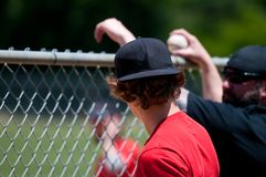 Teenage boy from behind looking through fence. Royalty Free Stock Photos