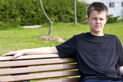 Teenage boy on bench. Portrait of a handsome teenage boy sitting on a bench Royalty Free Stock Photography