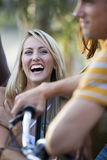 Teenage boy on bicycle, focus on teenage girl (17-19) laughing in background Stock Photos