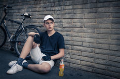 Teenage boy with bike in front of a brick wall. Teenager  with bike in front of a brick wall Royalty Free Stock Photography
