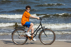 Teenage boy biking on beach Stock Image