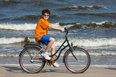 Teenage boy biking on beach Stock Image