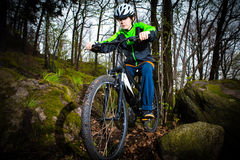 Teenage boy biking on forest trails Royalty Free Stock Photos