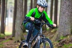 Teenage boy biking on forest trails Royalty Free Stock Image