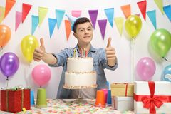 Teenage boy with a birthday cake. Holding his thumbs up royalty free stock image