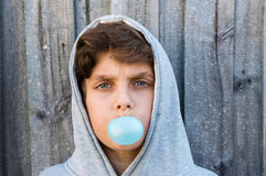 Teenage boy blowing blue bubble gum Stock Images