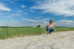 Teenage boy blowing soap bubble wand for making soap bubbles on dirt farm field road Stock Image