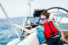 Teenage boy on board of sailing yacht. Teenage boy enjoying sailing on board a chartered catamaran or yacht stock images