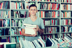 Teenage boy with book pile in shop Stock Photos