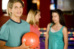 Teenage boy in a bowling alley, two girls in the background Stock Photos