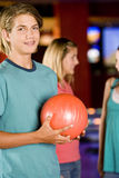 Teenage boy in a bowling alley, two girls in the background Royalty Free Stock Photos