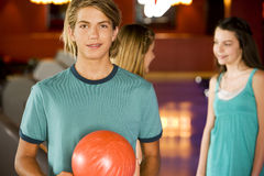 Teenage boy in a bowling alley, two girls in the background Royalty Free Stock Image