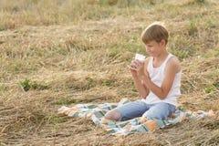 Teenage boy during break in farm field Royalty Free Stock Photo