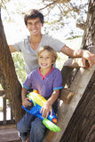 Teenage Boy And Brother Playing In Tree House Together Royalty Free Stock Images