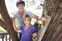 Teenage Boy And Brother Playing In Tree House Together Stock Images