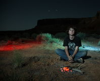 Teenage boy camping. Teenage boy lounging at a camp fire in the desert Royalty Free Stock Photos