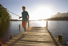 Teenage boy (12-14) carrying fishing rod and fish on lake jetty in sunshine, smiling (lens flare, backlit) Royalty Free Stock Photography