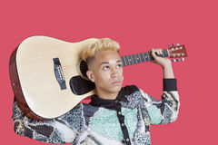 Teenage boy carrying guitar over his shoulder over pink background Royalty Free Stock Images