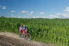 Teenage boy carrying his little sibling sister on baby bike seat on farm corn field summer dirt road Stock Photos