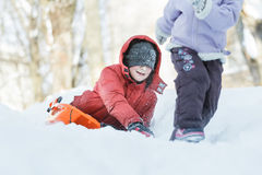 Teenage boy chasing after his sibling sister outdoors on snow hill Stock Photos