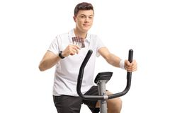 Teenage boy with a chocolate bar exercising on a stationary bike. Isolated on white background Royalty Free Stock Photography