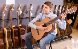 Teenage boy choosing best acoustic guitar in musical shop. Happy teenage boy choosing best acoustic guitar in musical shop Royalty Free Stock Photos