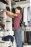 Teenage Boy Choosing Clothes From Wardrobe In Bedroom stock photography