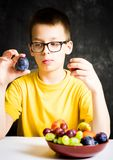 Teenage boy choosing between two kind of fruit Stock Photos