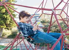 Teenage boy in climbing frame using smart phone Royalty Free Stock Photography