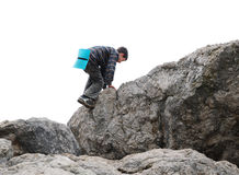Teenage boy climbing up rocks Stock Image