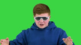 Teenage boy in cool shades talking to camera on a Green Screen, Chroma Key.