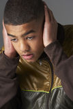 Teenage Boy Covering Ears With Hands Stock Photo