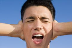 A teenage boy covering his ears. Stock Photography