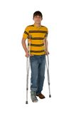 Teenage Boy On Crutches. With his right foot in a softcast brace isolated on a white background Stock Photos