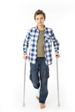 Teenage Boy with crutches and a bandage on his right leg. Isolated against white Royalty Free Stock Photo