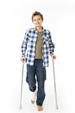 Teenage Boy with crutches and a bandage on his right leg Stock Photography