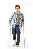 Teenage Boy with crutches and a bandage on his right leg. Isolated against white Stock Photo